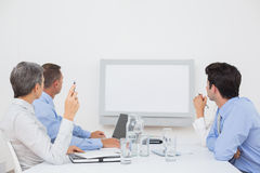 Business team looking at white screen Royalty Free Stock Photo