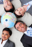 Business team lying on the floor around a globe. Business team lying on the floor around a terrestrial globe smiling at the camera Royalty Free Stock Images