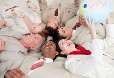 Business team lying and playing with a glob Stock Photography