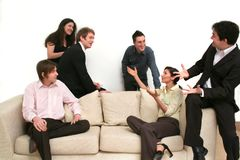 Business Team - Making The Point. Team of 6 business people on a sofa, having an excited discussion royalty free stock images