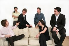 Business Team - Making The Point. Team of 6 business people on a sofa, having an excited discussion stock photo