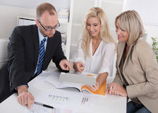 Business team of man and woman sitting around desk in a meeting royalty free stock photos