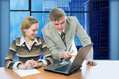 Business team man and woman work in office on laptop with view business buildings. And sky stock image