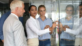 Business team in a meeting. Businesswoman sticking sticky notes on glass wall in office with her colleagues. Multi ethnic businesswoman sticking adhesive notes