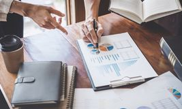 Business team are meeting and discussing marketing plan and pointing graph report analyzing financial figures denoting the stock image