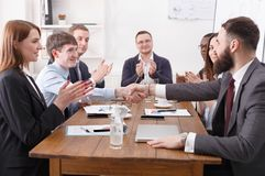 Business team meeting with male boss at wooden table. Workers applauding the speaker Stock Photography