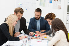 Business team in a meeting. Multiethnic diverse business team of dedicated young people sitting around a table in a meeting Stock Image