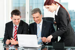 Business - team meeting in an office. With laptop, the boss with his employees Stock Photo