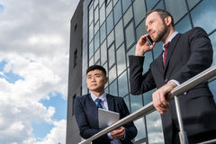 Business team meeting and using smartphone and digital tablet outdoors near office building Stock Photos