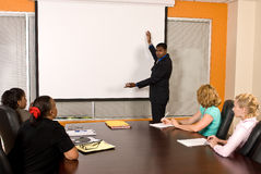 Business Team Meeting. A young business men gestures toward a drop-down projector screen while he talks to four female coworkers Royalty Free Stock Image