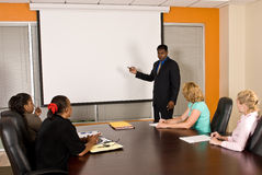 Business Team Meeting. A young business men points at a drop-down projector screen while he talks to four female coworkers Stock Images