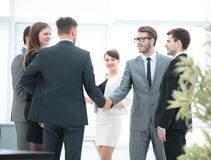 Business team meets business partners in the office.a friendly h. In the center of the photo .business partners shaking hands and smiling business team is ready Royalty Free Stock Images
