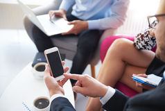 Business team. Mobilephone used while business meeting Stock Image