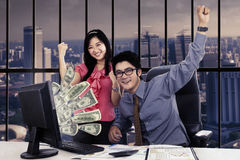 Business team with money on the computer Stock Photos