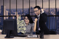 Business team with money on monitor Stock Image