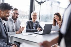 Morning briefing. Business team on a morning briefing; business meeting and presentation in a modern office. Focus on the women sitting royalty free stock photo