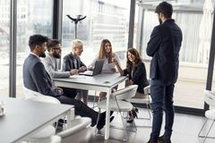 Morning briefing. Business team on a morning briefing; business meeting and presentation in a modern office. Focus on the women Royalty Free Stock Image