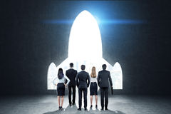 Business team near a black wall with a plane shaped opening, ton. Rear view of a business team standing near black wall with a plane shaped opening in it. Blue Stock Image