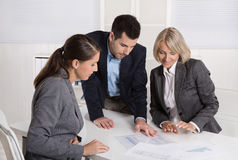 Free Business Team Of Man And Woman Sitting Around A Table Talking To Stock Photo - 46978900