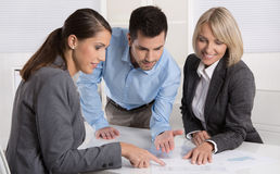 Free Business Team Of Man And Woman Sitting Around A Table Talking To Royalty Free Stock Image - 46978936