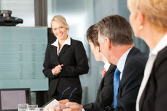 Business - team in office. Business - presentation within a team, a female, colleague is standing on the flipchart, one man is looking into the camera Stock Photo