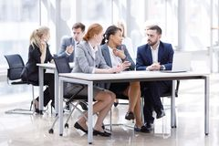 Business team in office. Business team sitting by the table with laptop and documents in office royalty free stock images