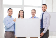 Business team in office with white blank board. Business and office concept - happy business team in office with white blank board Royalty Free Stock Photography