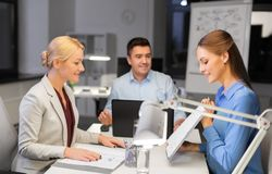 Business team with papers working late at office royalty free stock photography