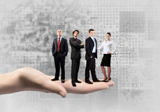 Business team. Business people of different professions standing on palm Royalty Free Stock Image