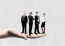Business team. Business people of different professions standing on palm Royalty Free Stock Photo