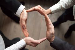 Business people join hands in circle, protection and support con stock photos
