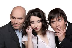 Business team phone. A young businesswoman holding a telephone receiver surrounded by two businessmen listening Stock Images