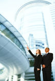 Business Team Pointing With Building Background. Business people standing in front of modern building. the woman pointing up to somewhere. concept for success or Stock Image