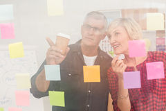 Business team pointing post its on the wall Royalty Free Stock Photography