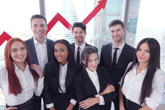 Business Team. Portrait of business team of men and women in office with arrow graph of income growth Royalty Free Stock Photography