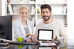 Business team. Portrait of business team working together at office. Young businessman holding hand a digital tablet with isolated screen while smiling Royalty Free Stock Image