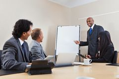 Business team in presentation. An African American business men giving a presentation to associates Royalty Free Stock Image