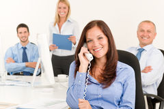 Business team pretty businesswoman calling phone. Business team pretty businesswomen calling phone happy colleagues around table Royalty Free Stock Photos