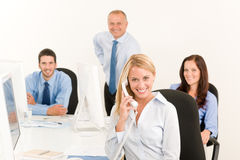 Business team pretty businesswoman calling phone. Business team pretty businesswomen calling phone happy colleagues around table Royalty Free Stock Photography