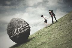 Business team pull a boulder with Success text. Picture of two young business team pull up a boulder on the hill with Success text Royalty Free Stock Photo