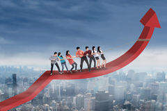 Business team pulling arrow upward Stock Photo