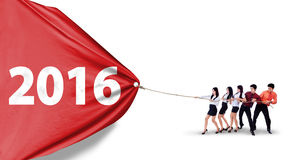 Business team pulling flag with numbers 2016 Stock Photo