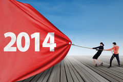 Business team pulling new year 2014 outdoor Royalty Free Stock Photos