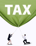 Business team pulling tax banner. Portrait of two business people pulling tax banner. Isolated on white background royalty free stock photos