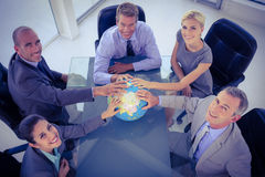 Business team putting hands on globe Royalty Free Stock Images