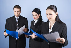Business team reading. Business team people holding blue folders with contracts and reading in front of blue background,check also Business people Royalty Free Stock Photography