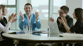 Business team rejoice success and applaud. Sitting at a table in light office stock footage