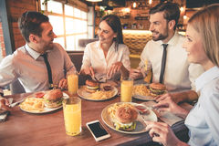 Business team resting in cafe. Business people are eating, talking and smiling while having lunch in cafe Stock Image