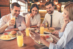 Business team resting in cafe. Business people are eating, talking and smiling while having lunch in cafe Royalty Free Stock Photo