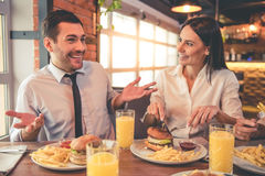 Business team resting in cafe. Business people are eating, talking and smiling while spending time together in cafe Royalty Free Stock Photography